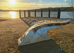 sunsets over the Plym Estuary with a giant leaf bench by the waters side. Plymouth public art