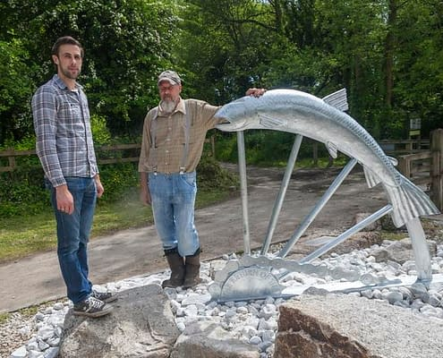 Thomas and Gary pose with the Camel Trail Salmon Sculpture made with St Tudy Primary School. Made by Thrussells. Poley Bridge, Cornwall. Public Art Cornwall
