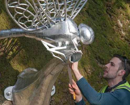 Thomas Thrussell checks over the giant metal dragonfly sculpture. Plymouth public art