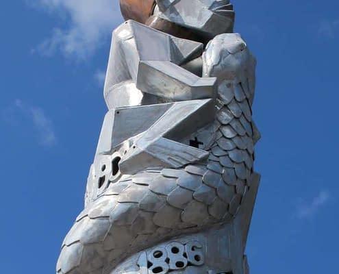 fertility figure sits a top of a metal sculptural column. Public Art Wales