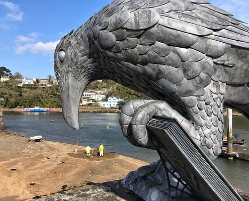'Rook With A Book' sculpture watches people on the beach below.