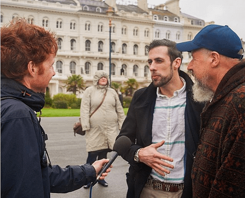 man interviews sculptors on Plymouth Hoe. Plymouth public art